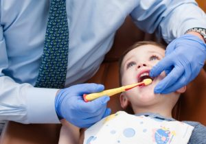 Orthodontist teaches child age 3-5 how to properly brush the teeth